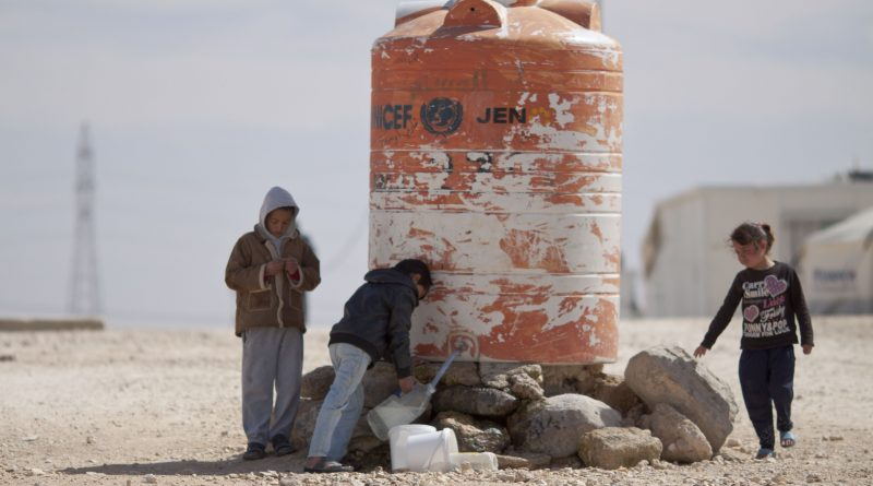 Syrian Children filling drinking water in tanks in Al-Za'tari camp for Syrian refugees in Jordan.