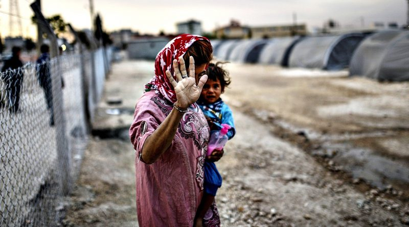 A Syrian Kurdish woman walks with her ba...A Syrian Kurdish woman walks with her baby on October 23, 2014,  in the Rojava refugee camp at Suruc in Sanliurfa province. Turkey said on October 21 that Kurdish peshmerga fighters based in Iraq have yet to cross into Syria from Turkish territory, a day after announcing it was assisting their transit to join the battle for the Syrian town of Kobane, also known as Ain al-Arab. It was seen as a major switch in policy by Turkey, which until now has refused to interfere in the over month-long battle for Kobane between Syrian Kurdish fighters and Islamic State (IS) jihadists. AFP PHOTO / BULENT KILICBULENT KILIC/AFP/Getty Images