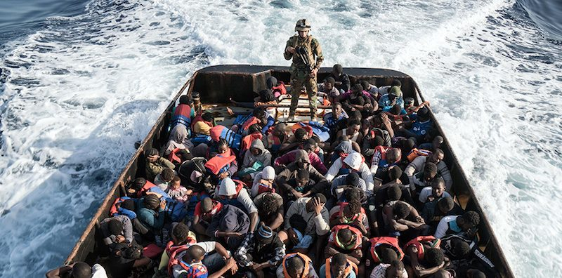 TOPSHOT - A Libyan coast guardsman stands on a boat during the rescue of 147 illegal immigrants attempting to reach Europe off the coastal town of Zawiyah, 45 kilometres west of the capital Tripoli, on June 27, 2017. More than 8,000 migrants have been rescued in waters off Libya during the past 48 hours in difficult weather conditions, Italy's coastguard said on June 27, 2017. / AFP PHOTO / Taha JAWASHI        (Photo credit should read TAHA JAWASHI/AFP/Getty Images)